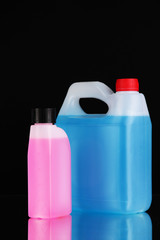 Blue and pink liquids for car in canisters on black background