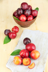 Ripe plums on wooden table close-up