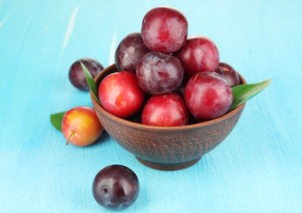 Ripe plums in bowl on wooden table close-up