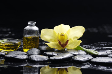 spa concept- orchid and black stones with palm leaf and candle