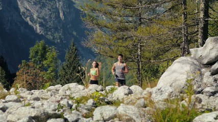 1of4 Young man and woman running on mountain trail, sport
