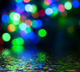Colorful circular bokeh reflected in water surface.