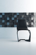 Black chair against minimalist modern mosaic wall