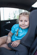 Pretty smiling child in car safety seat looking at camera