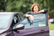 Laughing cheerful woman standing near new car with keys in hand