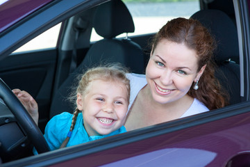 Happy toothy smiling mother with daughter on driver seat of car