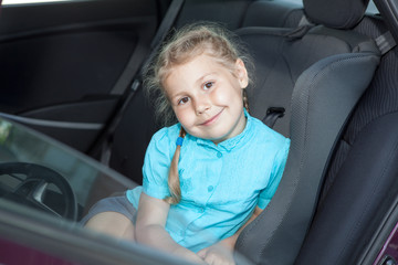 Small Caucasian girl in car safety seat going to journey