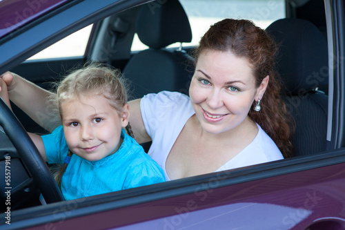 Happy mother with small daughter sitting together on driver seat