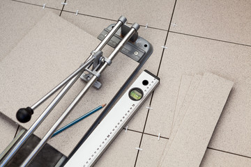 Level, tile-cutter and tiles