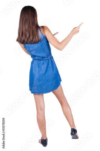 Back view of young brunette woman pointing at wall. cheerful gir