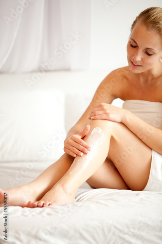 woman sitting and applying cream