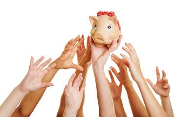 Hands reaching for money in piggy bank
