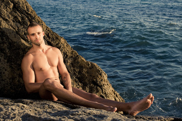 Fitness guy sitting on the rock. short haired.