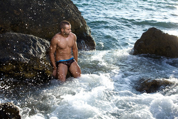 Guy with perfect body posing on the rocks