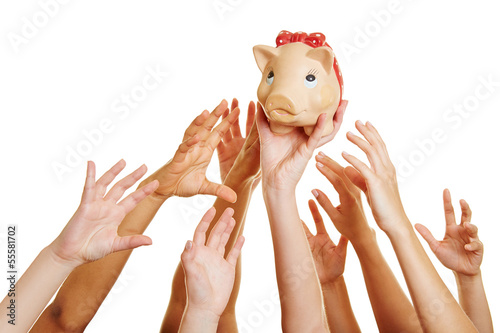 Hands reaching for money in piggy bank