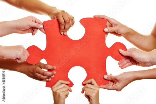 Hands holding red jigsaw puzzle