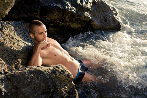 Fitness guy lying on the stone in water
