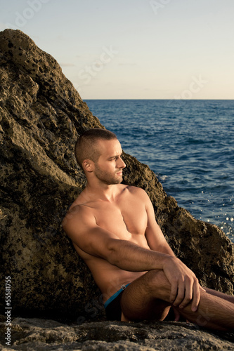 Fitness guy sitting on the rock. short haired