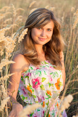 beautiful girl in a dress walks in the field