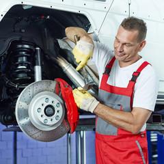 Car mechanic in a garage fixing the bracke