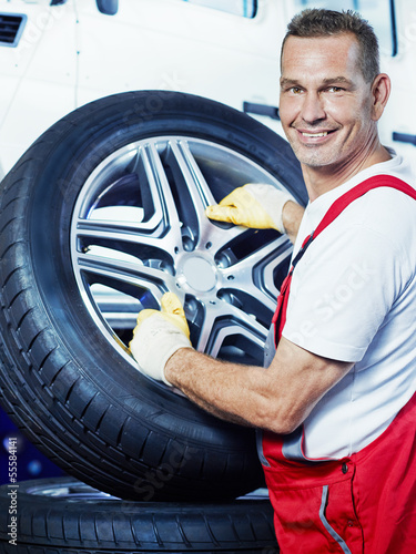 Auto mechanic changes car tyres in a garage