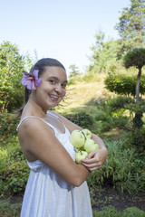 Cute natural looking young woman holding organic apples