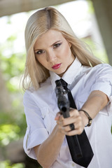 woman holding gun in blouse and tie