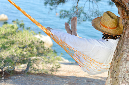 Man in hat in a hammock on pine tree in Crimea a summer day
