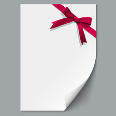 Sheet paper and red ribbon with gift bow