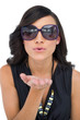 Elegant brunette wearing sunglasses sending kiss to camera