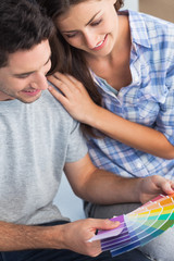 Couple looking at color samples to decorate their house