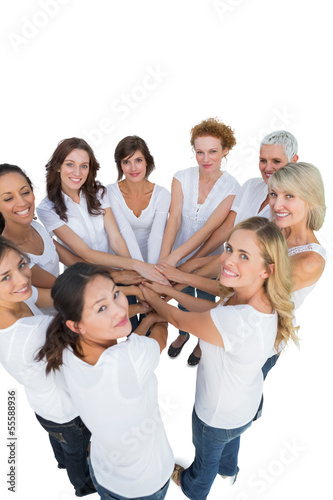 Happy female models joining hands in a circle and looking at cam