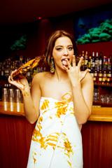 Attraktive brünette Frau in einer Bar isst Fleisch