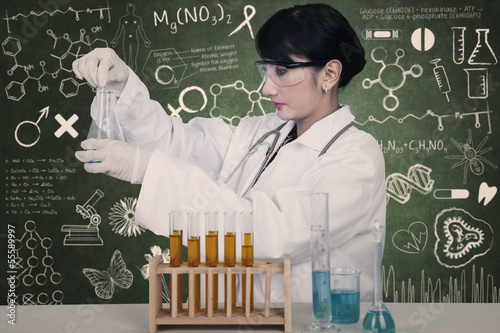 Beautiful female scientist working with formula