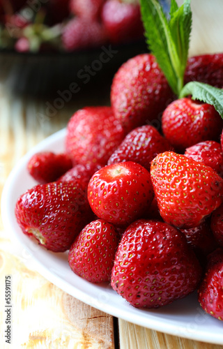 pile ripe strawberries on a white plate