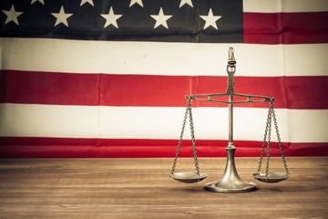 Law scales on table front of USA flag. Symbol of justice