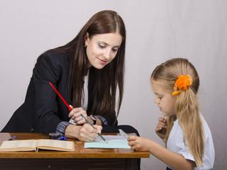Учитель обьясняет ученику примеры в тетрадке