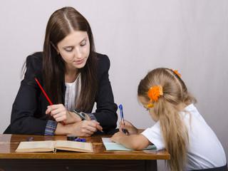 Учитель учит уроки с учеником сидя за столом