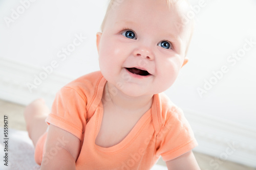 Cute baby girl with big eyes looking up, close up