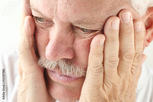 older man holds both hands up to his face
