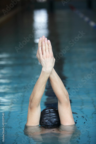 swimmer raising hands, preparing to swim in swimming pool