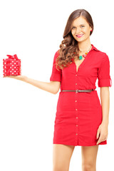 Attractive smiling woman in red dress holding a gift box