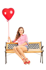 Beautiful smiling woman sitting on a bench holding a red heart