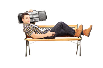 Guy with a boombox on his shoulder and lying on a wooden bench