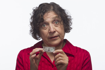 Older woman holding dollar bill with both hands, horizontal