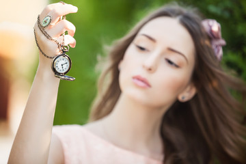 Portrait of young attractive woman with clock on chain