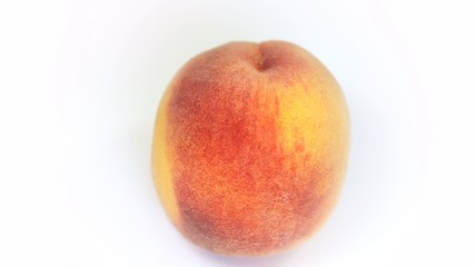 Ripe  peach fruit rotating on white background