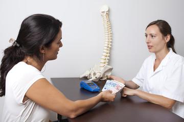 Patienin zahlt für medizinische Behandlung mit Bargeld