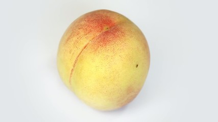 Ripe  peach fruit rotating on white background