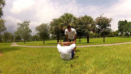 Young man doing sit-ups, exercising with personal trainer